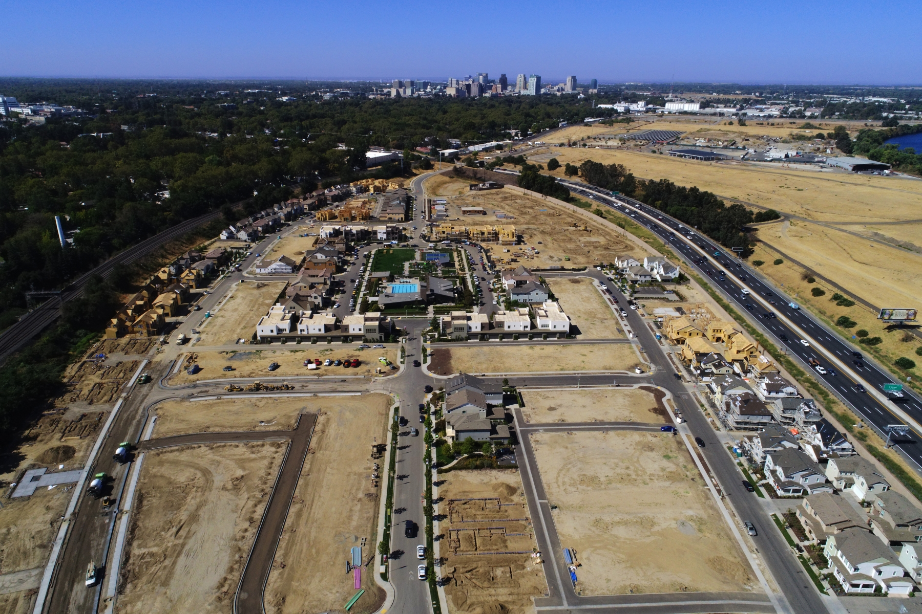 aerial view of development site with lots at various stages of construction and tall buildings in the distance