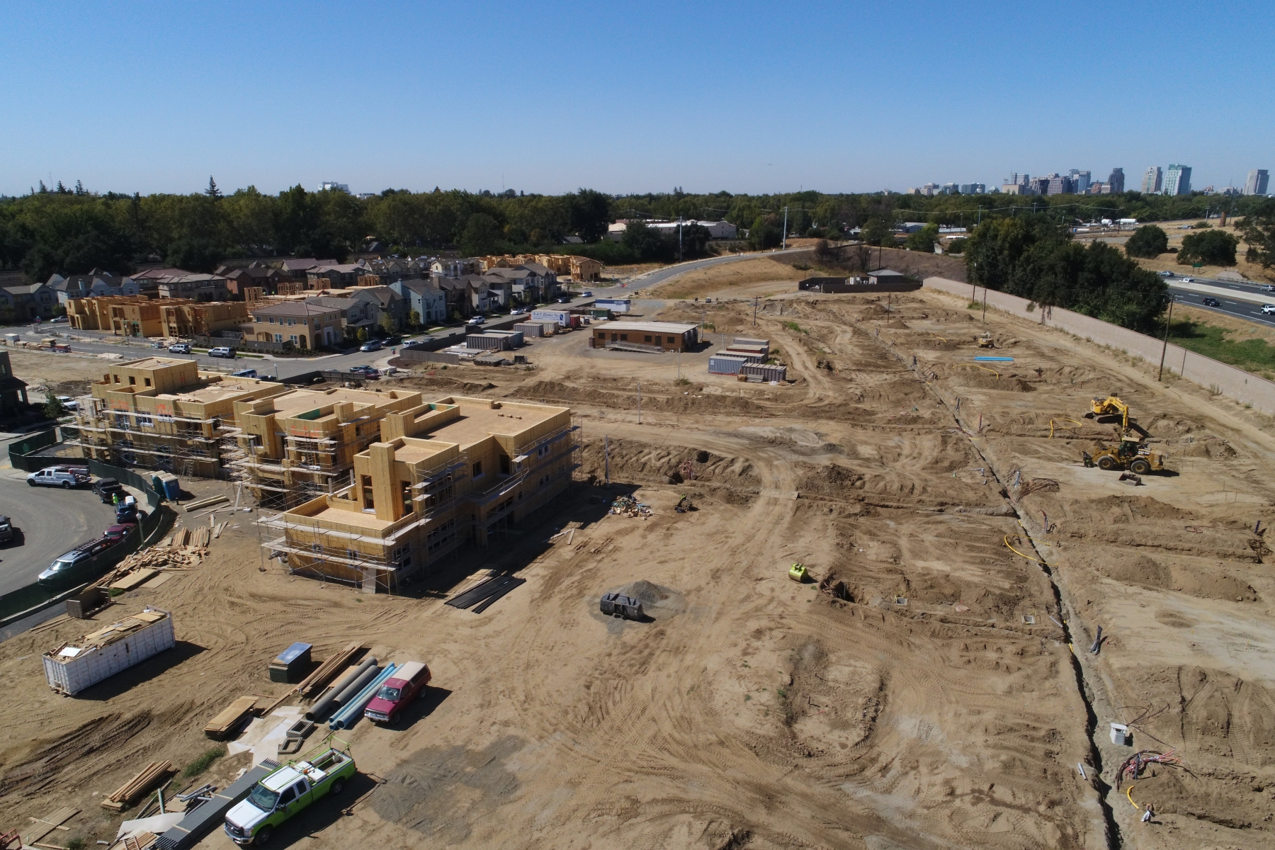 aerial view of development site with buildings and lots at different stages of construction