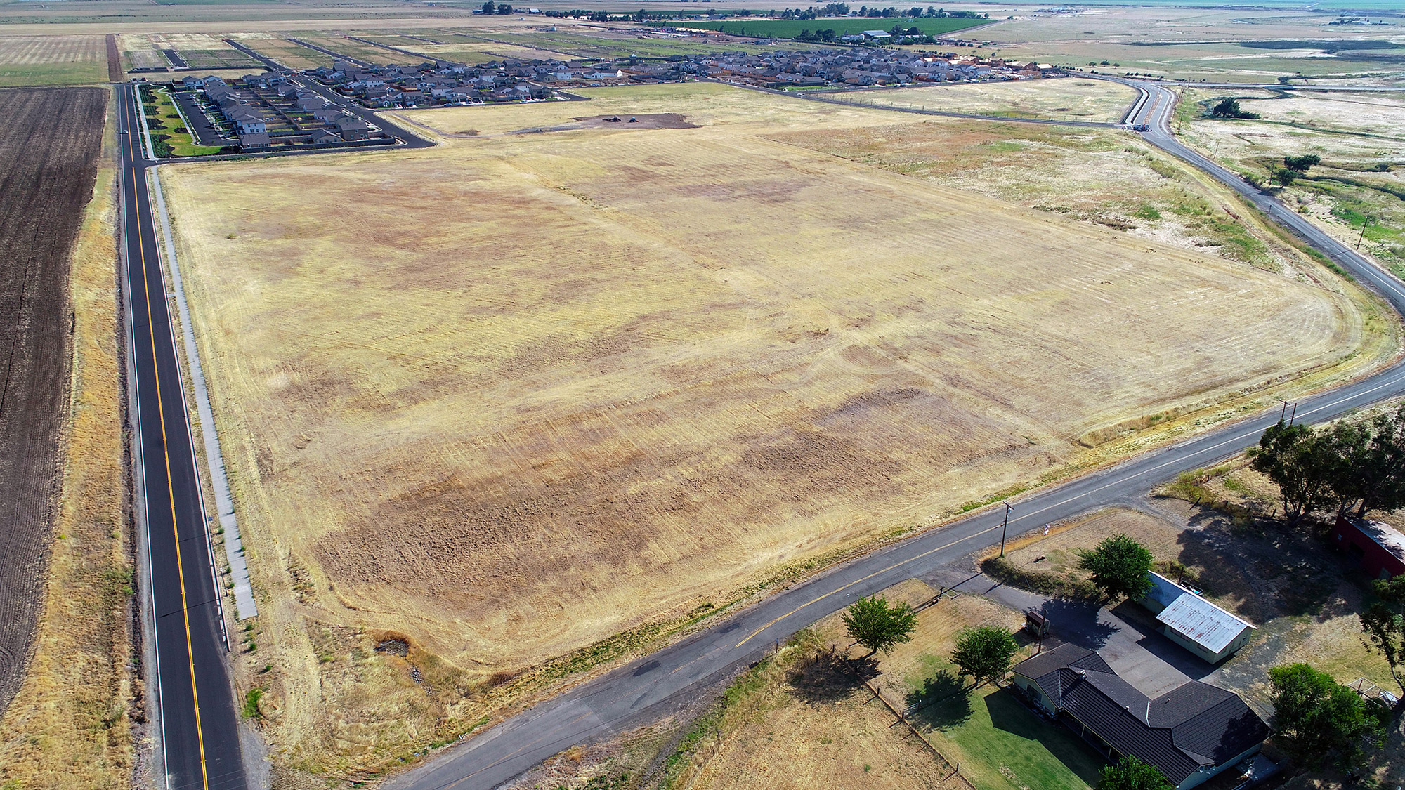 wide aerial view of a raw plot of land and a finished portion of the development in view behind it