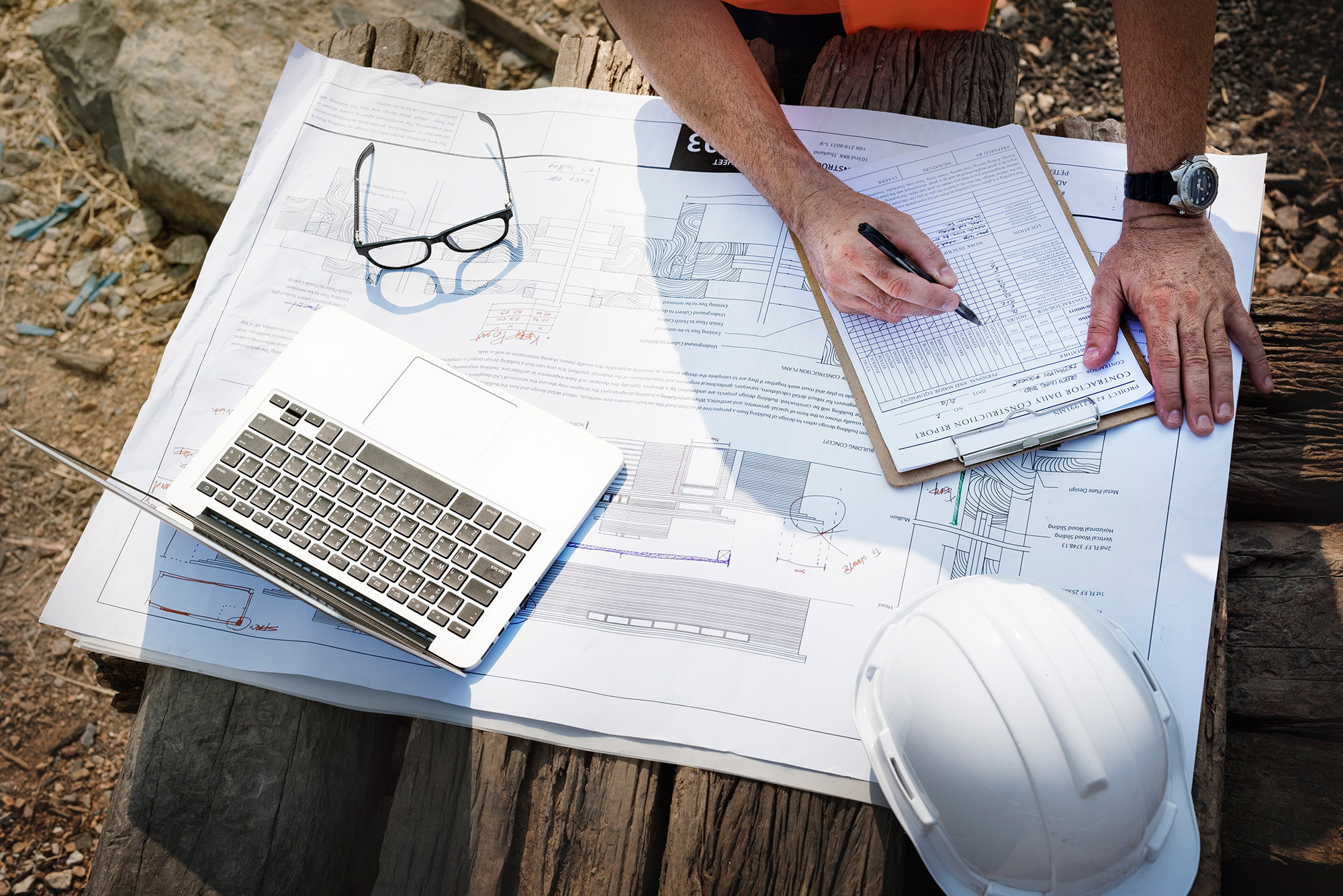 a set of architectural plans partially covered by a clipboard, laptop and hard hat at a construction site